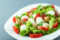 serving-fresh-salad-mozzarella-pearls-leafy-green-tomato-fried-golden-crunchy-croutons-close-up-low-angle-view-43418442